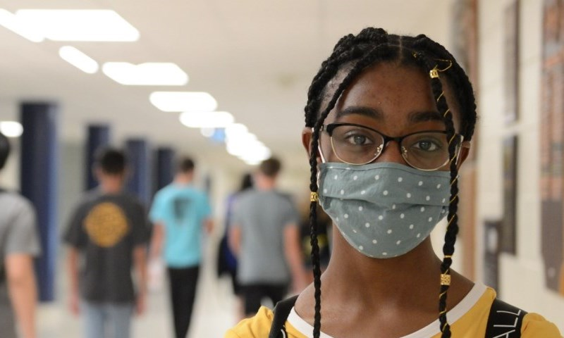 a student wearing a mask in a school hallway