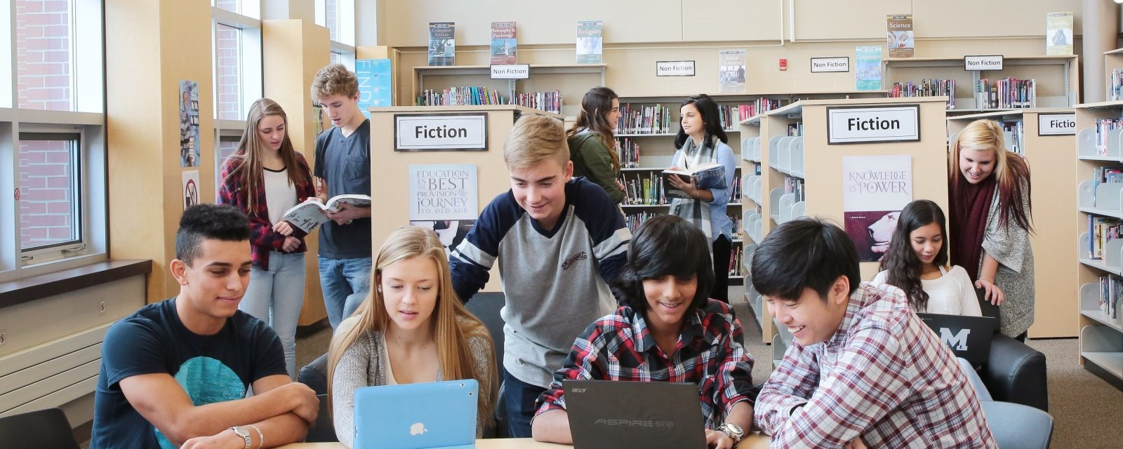 students working together in groups while seated in a library