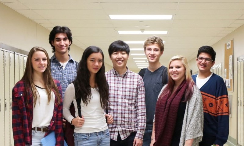 diverse group of students smiling and standing in a school hallway