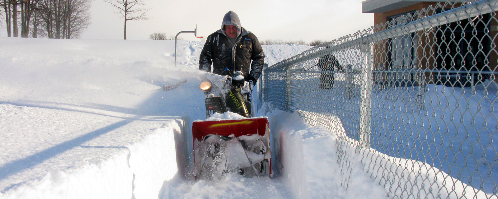 custodian using snowblower on snowday