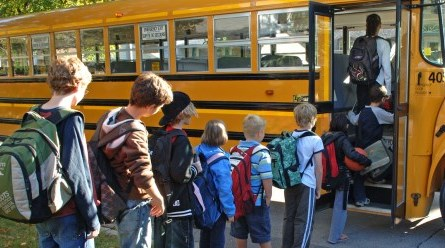 Students waiting in a line to board a schoolbus