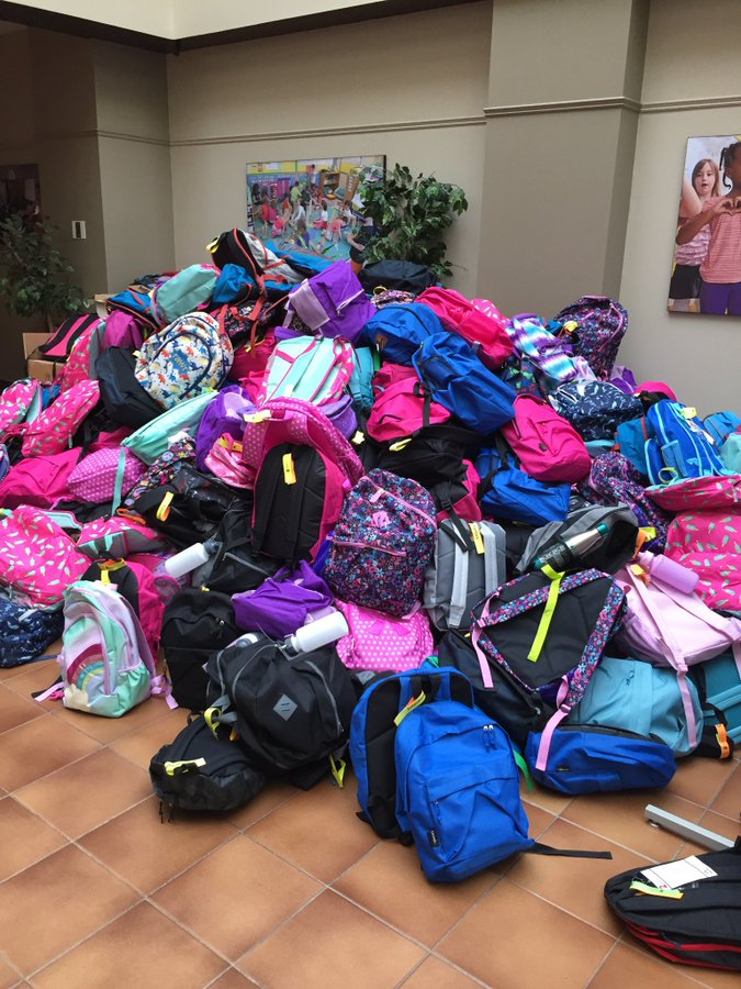 A large pile of backpacks, hundreds of them, stacked on top of one another, in an array of colours.