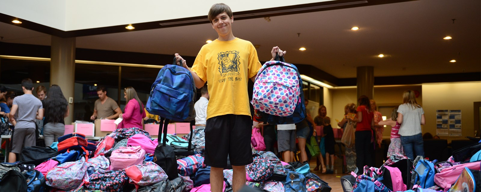 A volunteer helps stuff backpacks for the Supplies for Students program